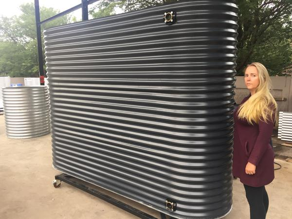 Lady standing alongside corrugated water tank